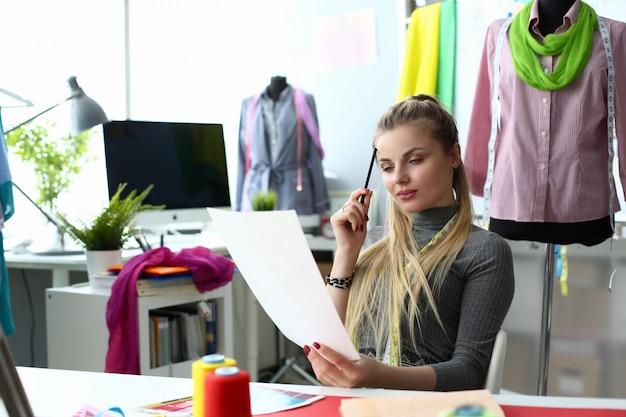 Creazione del processo di progettazione dei vestiti e concetto di cucito. bello sempstress che pensa lavorando allo schizzo del vestito.