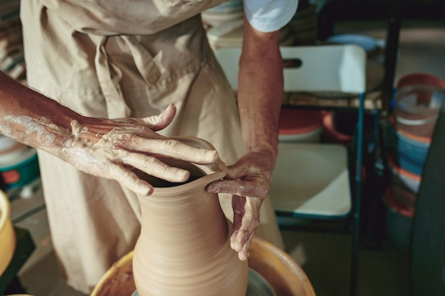 Creazione di un barattolo o vaso di primo piano di argilla bianca. maestro coccio. mani dell'uomo che fanno macro brocca di argilla. lo scultore del laboratorio fa una brocca con un primo piano di terracotta. tornio da vasaio contorto.