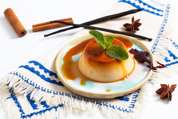 Crema al caramello o panna cotta della vaniglia con i baccelli di vaniglia e le spezie su fondo bianco