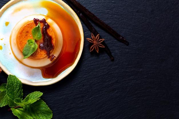 Crema alla vaniglia al caramello o panna cotta con baccelli di vaniglia e spezie su pietra nera backgr