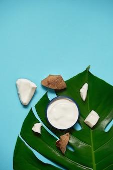 Crema bianca in un barattolo con cocco, mandorle su foglia blu e tropicale. concetto di bellezza e assistenza sanitaria. piano minimalista disteso con spazio di copia. vista dall'alto. cura della pelle naturale cosmetica