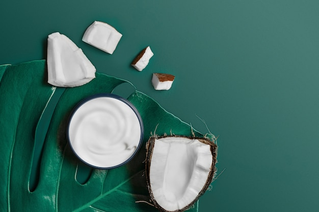 Crema bianca in un barattolo su una foglia tropicale esotica con cocco su eden verde scuro alla moda. concetto di bellezza e assistenza sanitaria. piano minimalista disteso con spazio di copia. vista dall'alto