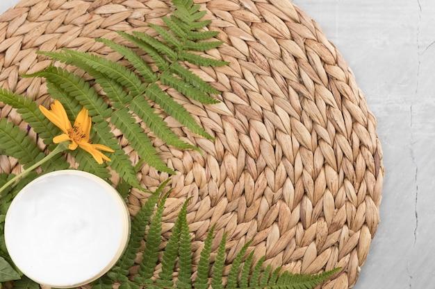 Crema corpo piatta e composizione floreale