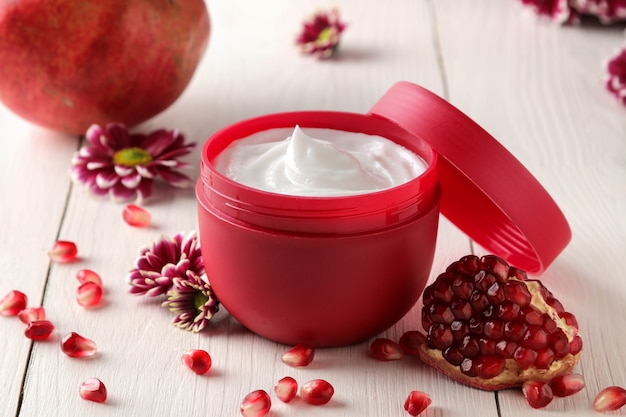 Crema cosmetica in un barattolo rosso con fiori e melograno fresco su un tavolo di legno bianco.