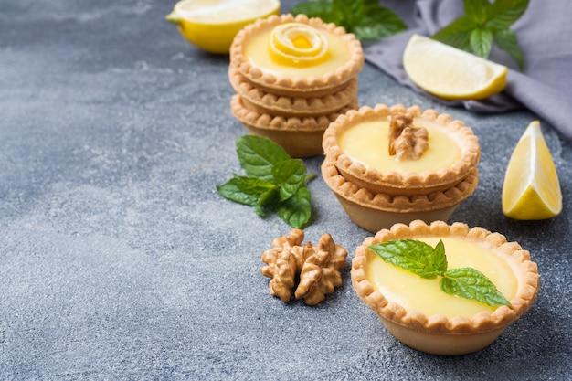 Crema di limone fatta in casa in tortine con foglie di menta e limone fresche.