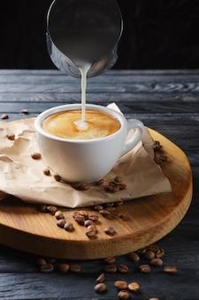 Crema di versamento alla tazza di caffè. un flusso di latte versa nella tazza.