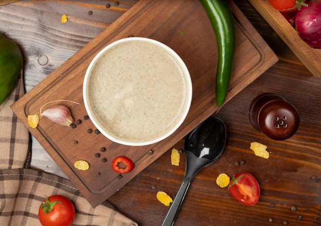 Crema di zuppa di funghi in tazza usa e getta servita con verdure verdi.
