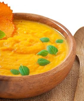 Crema di zuppa di zucca in una ciotola di legno