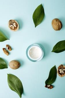 Crema gialla a base di ingredienti naturali su uno sfondo blu pastello con foglie verdi e noci. il concetto di creare essenze da ingredienti naturali