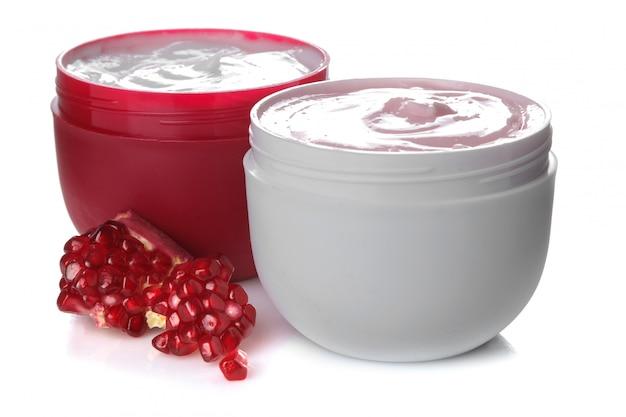 Crema in un barattolo bianco e rosso accanto al melograno fresco su bianco