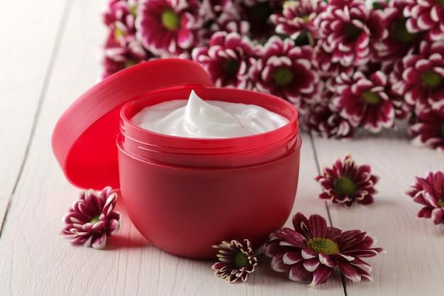 Crema in un primo piano vaso rosso e fiori di crisantemo su un tavolo di legno bianco.