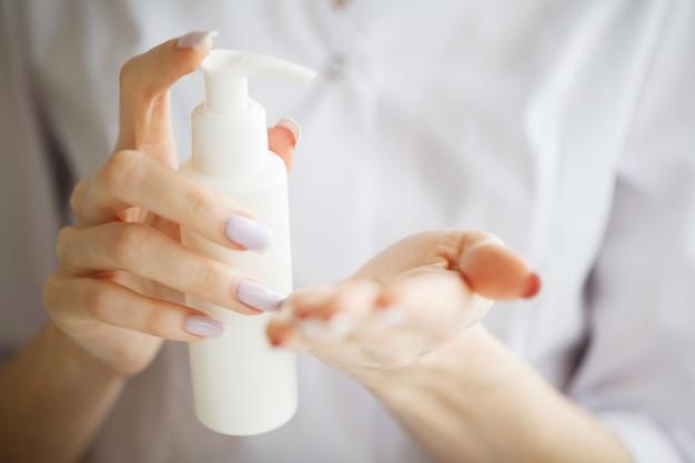 Crema mani donna. primo piano delle mani con crema o soluzione terapeutica