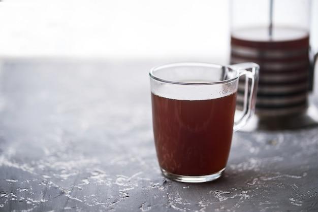 Crema pasticcera caffè in una tazza di vetro, cucchiaio, zollette di zucchero, crema pasticcera su uno sfondo di cemento.