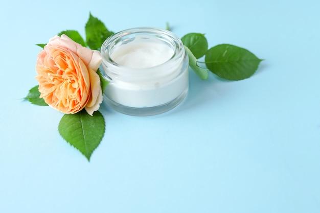 Crema per il viso con fiori a base di erbe sul tavolo blu