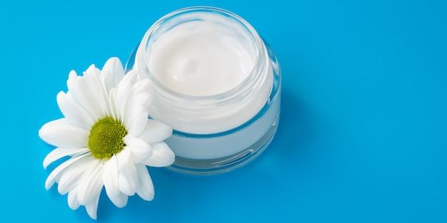 Crema per il viso in un barattolo di vetro con un fiore di camomilla su sfondo blu.
