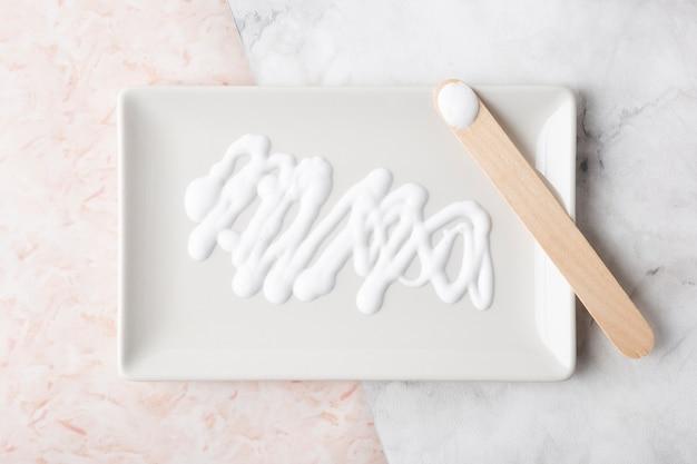 Crema per la cura della pelle vista dall'alto sul piatto bianco