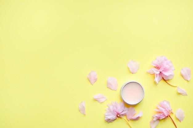 Crema per le mani, balsamo per le labbra e sapone su uno sfondo giallo.