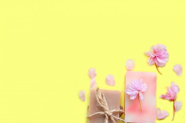 Crema per le mani, balsamo per le labbra su uno sfondo giallo, petali di fiori.