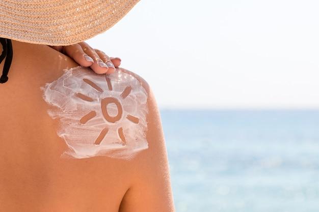 Crema solare a forma di sole sulla spalla di una donna abbronzata