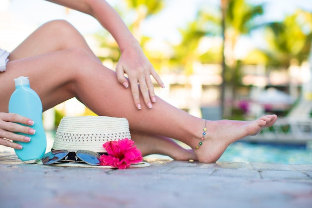 Crema solare, cappello, occhiali da sole, fiori e gambe femminili abbronzate vicino alla piscina