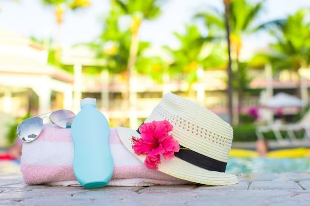 Crema solare, cappello, occhiali da sole, fiori e torre vicino alla piscina