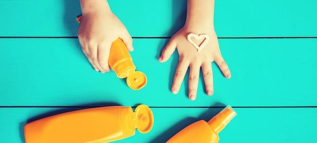 Crema solare sulla mano di un bambino.