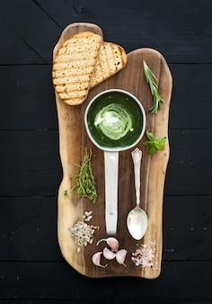 Crema-zuppa di spinaci verde fatta in casa in una paletta di metallo con fette di pane grigliato, erbe, spezie su tavola di legno rustico su sfondo nero