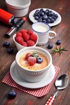 Crème-brulée con frutti di bosco e bastoncino di vaniglia, primo piano