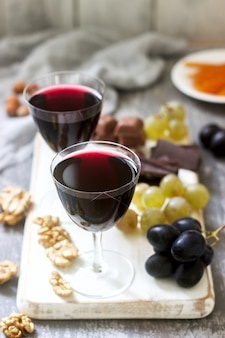 Creme de cassis liquore fatto in casa servito con uva, noci e cioccolato. stile rustico.