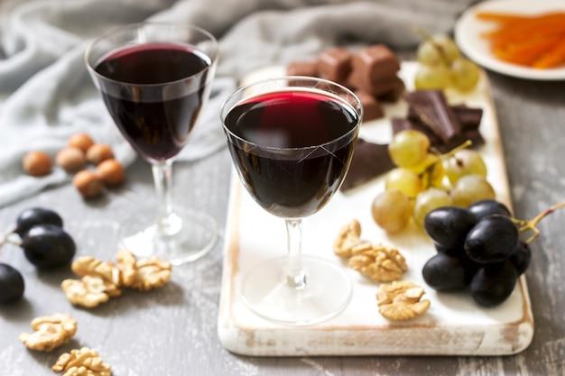 Creme de cassis liquore fatto in casa servito con uva, noci e cioccolato
