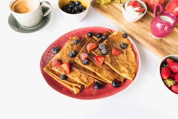 Crepe triangolare con fragole e mirtilli sul piatto rosso su sfondo bianco