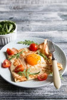 Crepes con uova, formaggio, foglie di rucola e pomodori. galette completa.