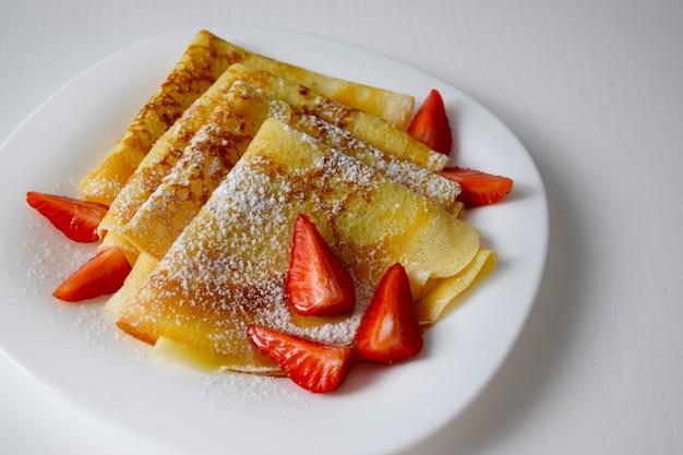 Crepes fatte in casa, gustose frittelle sottili con fragole e zucchero a velo sul piatto bianco