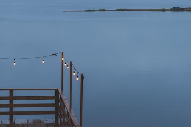 Crepuscolo, cielo di colore grigio al lago, lampade elettriche come ghirlanda e terrazza in legno, molo. atmosfera romantica della sera. terrazza del caffè. ghirlanda retrò per la decorazione domestica.