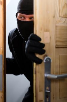 Crimine di furto con scasso - ladro che apre una porta