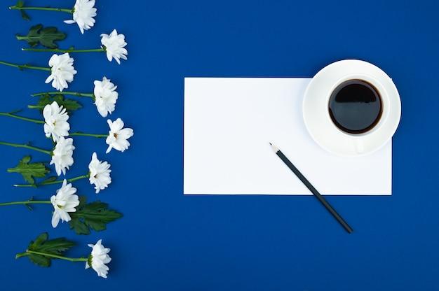Crisantemi bianchi con la nota della carta di carta su spazio blu. per fare un elenco di concetti. motivo floreale