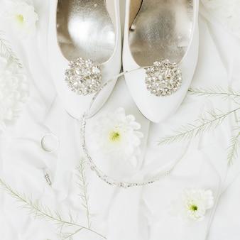 Crisantemo; fedi nuziali; corona vicino alle scarpe da sposa sulla sciarpa