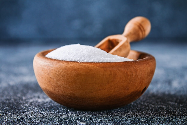 Cristalli di sale poco profondo in una ciotola di legno su un tavolo grigio scuro.