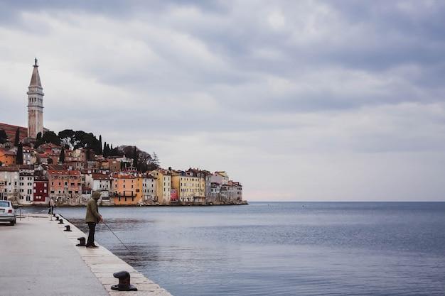 Croazia, rovigno - 29 marzo 2018, uomo che pesca in riva al mare vicino al colorato centro storico di rovigno, istria, croazia