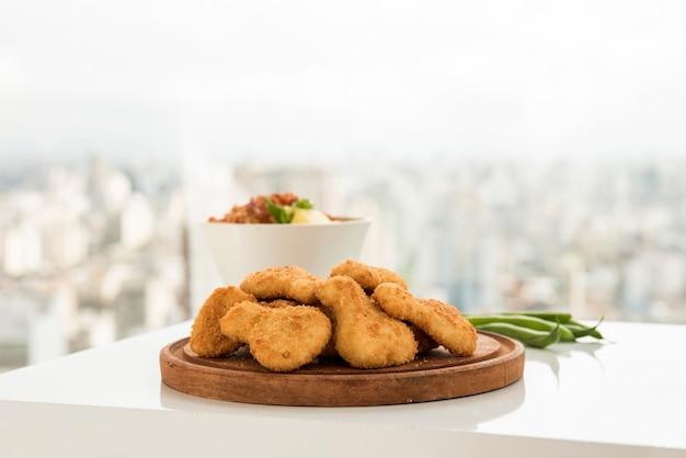 Crocchette di pollo croccanti servite sul piatto di legno