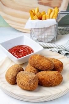 Crocchette di prosciutto e pollo con patatine e pomodoro