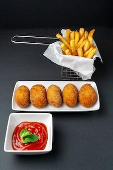 Crocchette gourmet con chip su sfondo scuro
