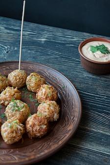 Crocchette vegetariane di patate e cavoli con salsa, verdure ed erbe aromatiche. imballato in pergamena. gustoso e soddisfacente. fondo in legno scuro vista laterale.