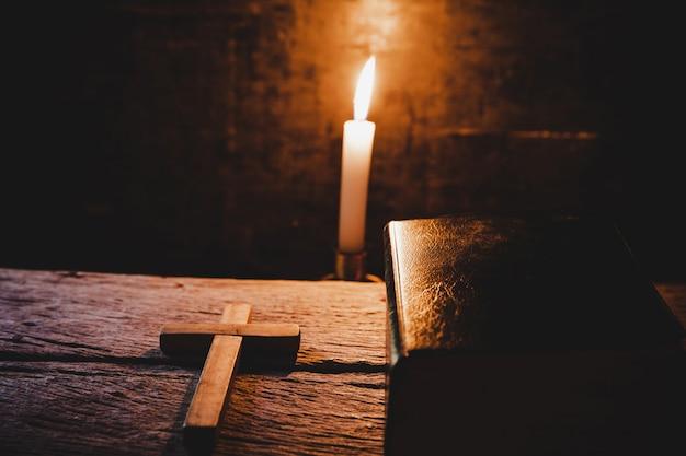 Croce con la bibbia e la candela su un vecchio tavolo di legno di quercia.
