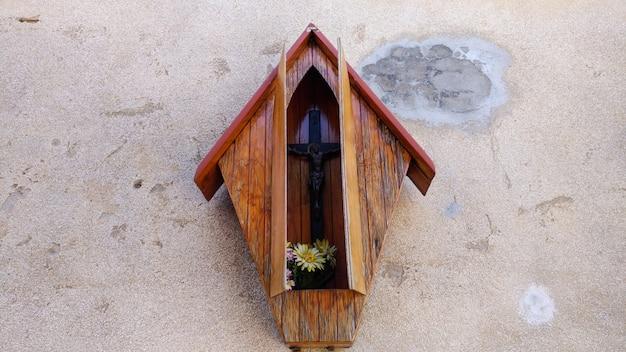 Croce di legno sul muro di mattoni in pietra in scatola