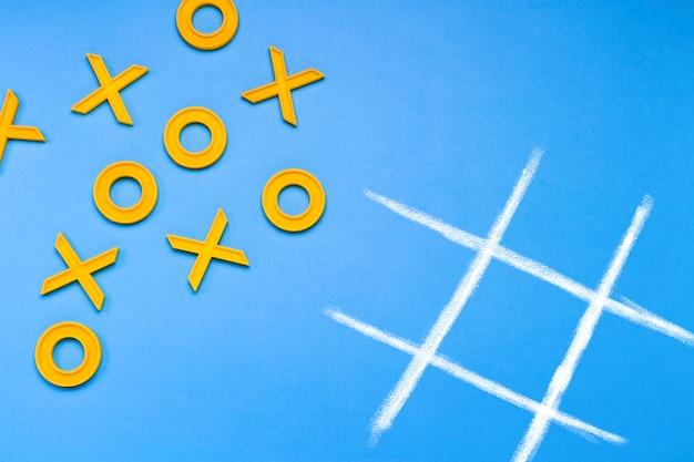 Croci di plastica gialle e una punta e un campo rigato per giocare a tic-tac-toe su un blu
