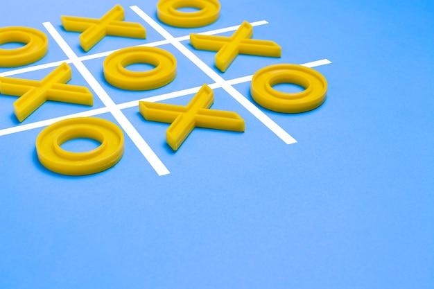 Croci di plastica gialle e una punta e un campo rigato per giocare a tic-tac-toe su una superficie blu. concept xo win challenge. gioco educativo per bambini