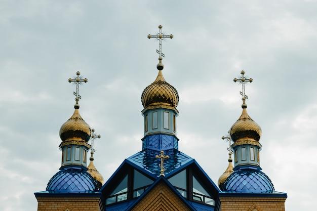 Croci ortodosse orientali su cupole d'oro cupole againts cielo blu con nuvole