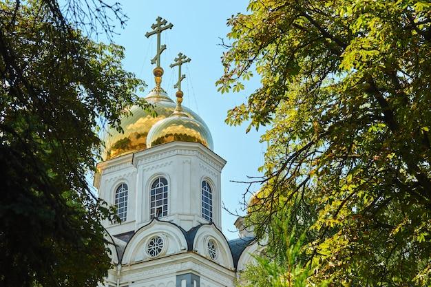 Croci ortodosse orientali su cupole d'oro (cupole) contro cielo blu