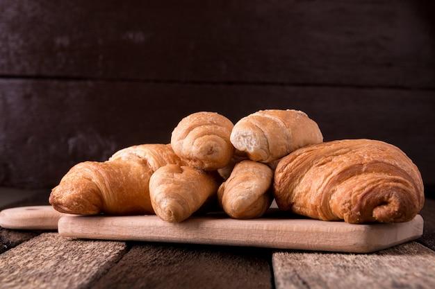 Croissant a bordo su fondo di legno. stile rustico.